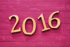 Gold 3D 2016 Lying on Table for New Year Concept. Gold 3D 2016 Lying on a Wooden Magenta Table for New Year Concept Stock Image