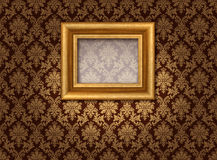 Gold and damask. Classic golden picture frame in spotlight against damask style wallpaper Royalty Free Stock Image