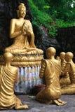 Gold, das Buddha umgeben von den Mönchkursteilnehmern sitzt Lizenzfreie Stockfotos