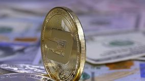 Gold Dash Coin and Bills of Dollars are Rotating. Different Crypto Currency Close-up. Macro. Dollar banknotes of various denominations on which lies the stock video footage