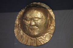 Gold death-mask  in Athens museum of Arheology. Gold death-mask  of a man in Athens. It is made of gold sheet with repousse details. The gold mask is the Royalty Free Stock Images