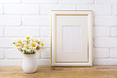 Gold decorated frame mockup with chamomile bouquet in rustic vas stock images