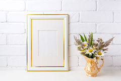Gold decorated frame mockup with chamomile and grass in golden v Stock Images