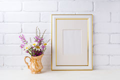 Gold decorated frame mockup with chamomile and purple flowers in royalty free stock photo