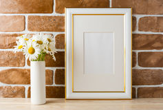 Gold decorated frame mockup with daisy bouquet exposed brick wal Royalty Free Stock Images
