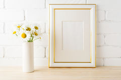 Gold decorated frame mockup with daisy near painted brick wall Stock Photos