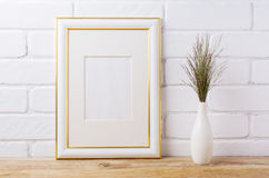 Gold decorated frame mockup with dark grass in elegant vase. Gold decorated frame mockup with dark meadow grass in elegant vase near painted brick wall. Empty Royalty Free Stock Photo