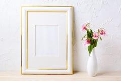 Gold decorated frame mockup with flower bouquet in elegant vase Stock Image