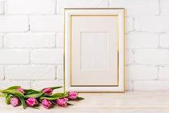 Gold decorated frame mockup with magenta tulips bouquet. Gold decorated frame mockup with bright magenta pink tulip bouquet. Empty frame mock up for presentation stock image