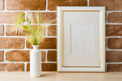 Gold decorated frame mockup with ornamental grass exposed brick Stock Photography