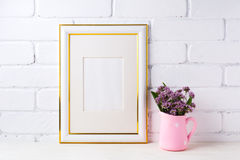 Gold decorated frame mockup with purple flowers in pink rustic p Stock Image