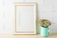 Gold decorated frame mockup with soft pink flowers and bricks Stock Photo