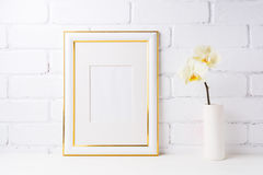 Gold decorated frame mockup with soft yellow orchid in vase Stock Photo