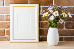 Gold decorated frame mockup with wildflowers bouquet exposed bri Stock Image