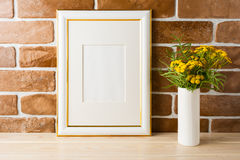 Gold decorated frame mockup  yellow flowers near exposed brick w. Gold decorated frame mockup with wild deep rich yellow flowers in vase near exposed brick walls Royalty Free Stock Image