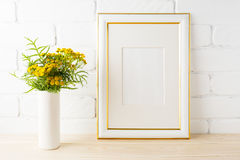 Gold decorated frame mockup  yellow flowers near painted brick w Stock Image