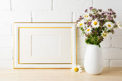 Gold decorated landscape frame mockup with blooming wildflower b Stock Images
