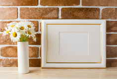 Gold decorated landscape frame mockup with daisy bouquet in vase Royalty Free Stock Images