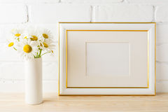 Gold decorated landscape frame mockup with daisy flower in vase. Gold decorated landscape frame mockup with wild daisy flower in styled vase near painted brick Stock Images