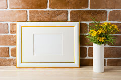 Gold decorated landscape frame mockup near exposed brick walls Royalty Free Stock Images