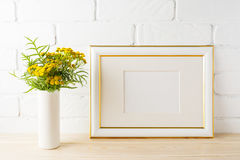 Gold decorated landscape frame mockup near painted brick walls Stock Photos