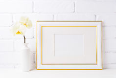 Gold decorated landscape frame mockup with soft yellow orchid in stock photography