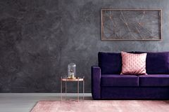 Sophisticated living room interior. Gold decoration on concrete wall above violet couch with pink pillow in sophisticated living room interior Stock Image