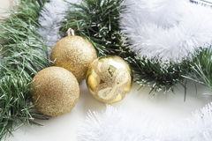 Gold decorative Christmas ball and green and white garland on white background Royalty Free Stock Photos