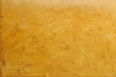 Gold decorative plaster imitating marble surface. Background Royalty Free Stock Photos