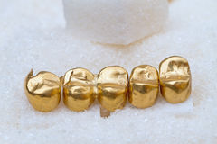 Gold dental crowns on sugar Royalty Free Stock Photography