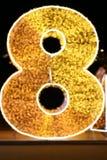 Gold der Alphabet-Zahl-acht, unscharfe Gussart funkelndes Glanzgelb des Goldes 8 Bokeh-Buchstaben acht der bunten Beleuchtung auf Lizenzfreie Stockfotografie