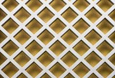 Gold diagonal pattern. Image of a metal lattice over a gold -colored wall royalty free stock photo
