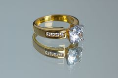 Gold diamond ring. On the reflective background Stock Images