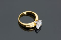 Gold diamond ring on the reflective background Stock Image