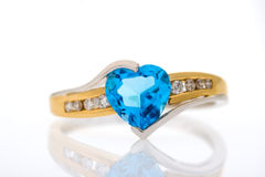 Gold diamonds ring with blue sapphire heart shaped. Gold ring with blue sapphire heart shaped and with diamonds on a white background with reflection royalty free stock photography