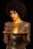 Gold digger. Achieved her goal - she has lots of money to spend for her amazing dress, interesting coverage and special golden cupcake on plate made of the same royalty free stock image