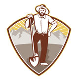 Gold Digger Miner Prospector Shield. Illustration of a gold digger miner prospector with shovel spade done in retro style set inside shield with mountains in Stock Image