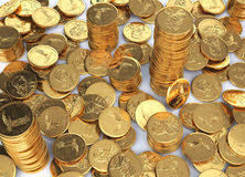 Gold dollar coins spread on a white surface and few stacks. Gold dollar coins spread on a white surface and few stacks between them Royalty Free Stock Photo