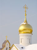 Gold domes of church. Church in Russia with snow on a roof and domes Royalty Free Stock Images