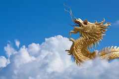 Gold dragon fly over blue sky and big white cloud. Royalty Free Stock Photo