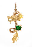 Gold pendant with emerald in the shape of a dragon Stock Images
