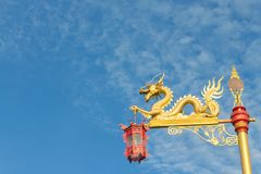Gold dragon on the pole with the red lantern. The gold dragon on the pole with the red lantern with sky background Royalty Free Stock Image