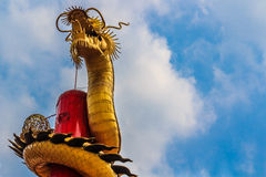 Gold dragon slithering into the sky. Golden Chinese Dragon Wrapped around red pole Royalty Free Stock Image
