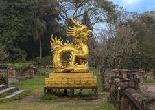 Gold dragon statue on the terrace of the garden of the Forbidden city,Imperial City inside the Citadel, Hue, Vietnam. Pictured is a golden dragon sculpture on stock photography