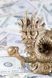 Gold dragon, symbol of 2012 year against dollars royalty free stock photography