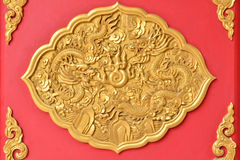 Gold dragon texture on Thai temple wall. Gold dragon texture in Thai temple on red wall Royalty Free Stock Image
