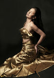 Gold dresses. Woman beautiful gold dresses young Stock Photography