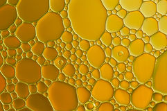 Gold drops of oil and air bubbles on the water Stock Photo