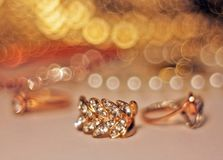 Gold earring with diamonds and bokeh stock photography