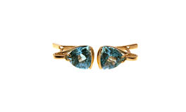 Gold earrings with a dark blue topaz Stock Image